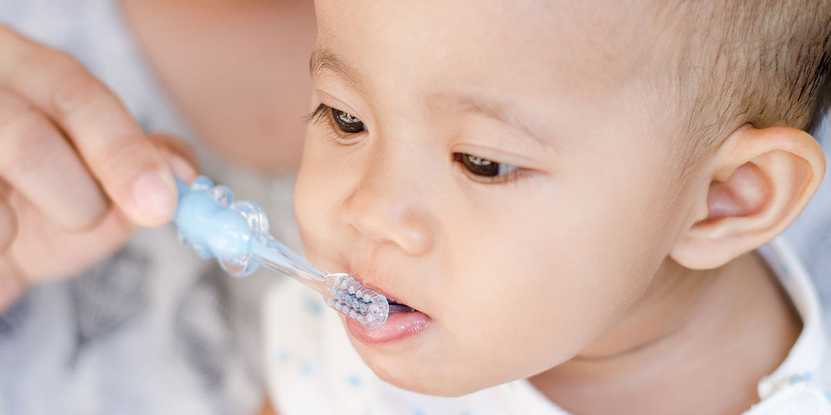 Parent brushing infant's teeth