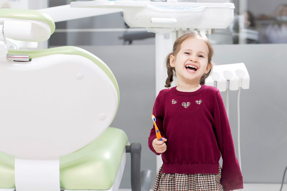young girl next to dental chair smiling, holding toothbrush
