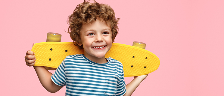 young boy holding yellow skateboard