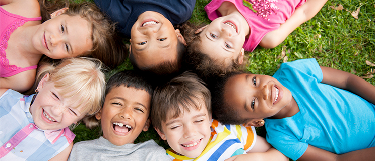 a group of children laying on the grass, looking up and smiling